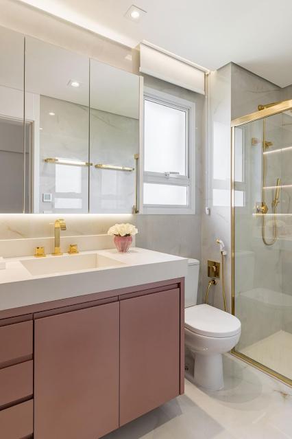 Banheiro pequeno neutro com armário planejados rosa e dourado