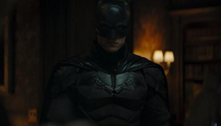 Imagem: o ator Robert Pattinson como o Batman, em traje de morcego, uma máscara preta com pontas, uma capa preta de couro e um traje metálico com um morcego no peito feito de pedaços de metal.
