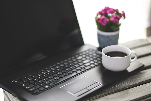 Mesa de trabalho com notebook, café e flores