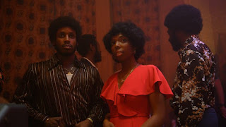 Three people in 1970s dress at a party