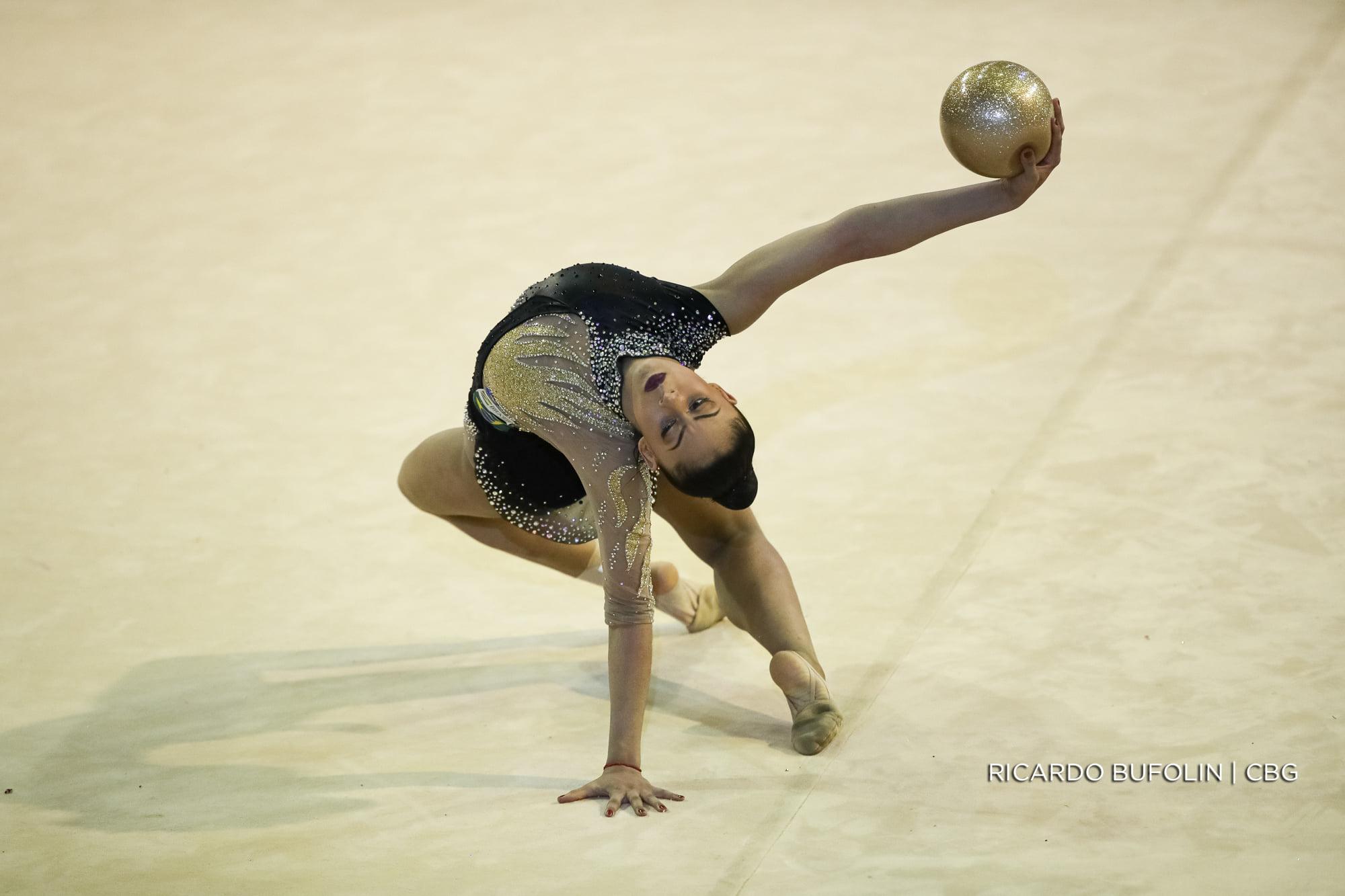 Bárbara Domingos usa um collant preto enquanto faz sua apresentação com a bola