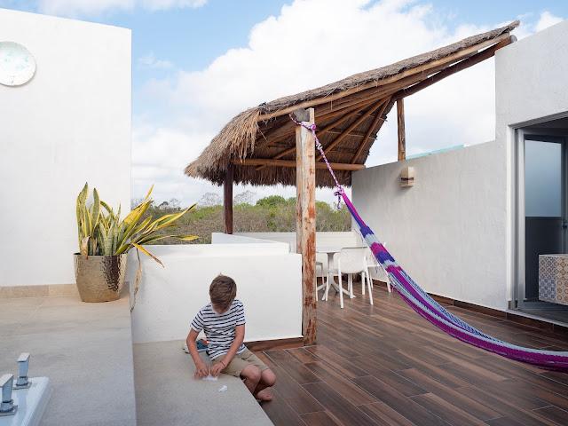 Niño sentado en una terraza con hamaca y mesa
