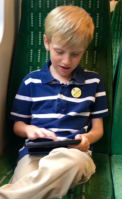 child wearing autism awareness badge on train
