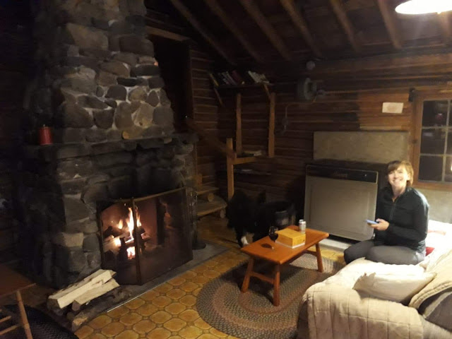 woman in cabin in front of stone fireplace