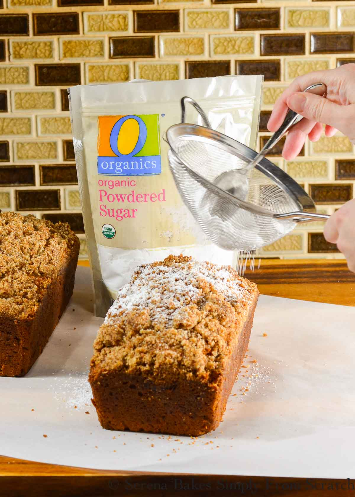 Baked Pumpkin Bread with Streusel being lightly dusted with powdered sugar.