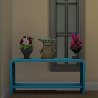 Screenshot from Sims4 game of a table with vase of roses, space rock, and licensed ornament of Baby Yoda named The Child Statue