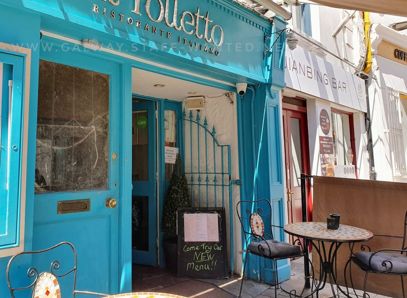 Bright turquoise shop front  in an Italian restaurant in the sunshine under a canopy.