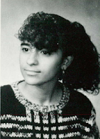 A high school yearbook photo of an Hispanic girl with hair in an '80s style, wearing dangling earrings and a dark sweater with a lighter, variegated pattern running both vertically and horizontally