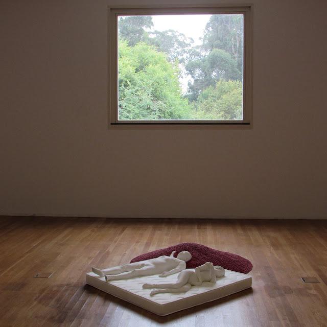 Obra de arte representando um homem e uma mulher deitados num colchão junto de grãos vermelhos próximos de uma janela de vidro