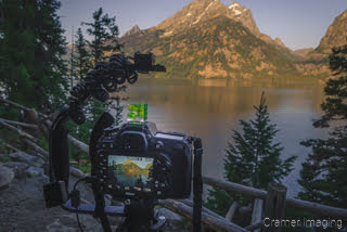Cramer Imaging's photograph of a camera on a tripod taking a lake picture at Grand Teton National Park Wyoming at sunrise
