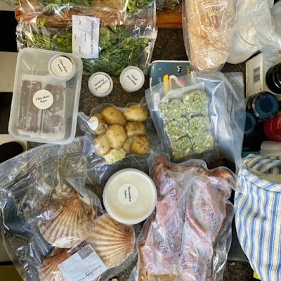 An array of pre-packed food, including sauces in tubs, and scallops and lobster in plastic bags.