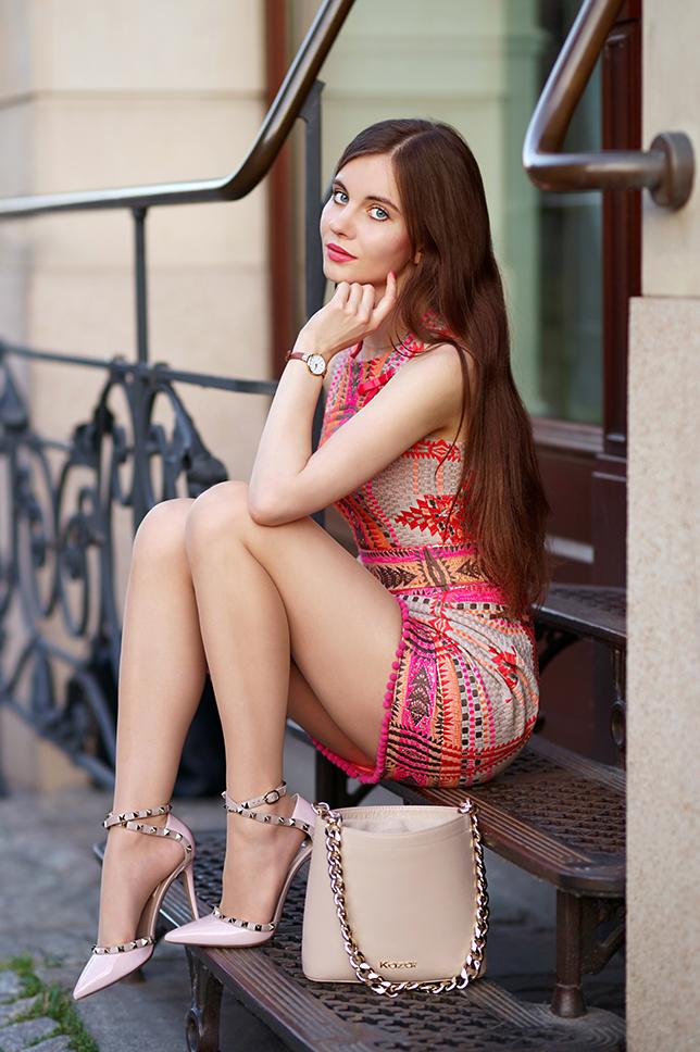 Wzorzysta kolorowa sukienka, cieliste rajstopy i różowe szpilki z ćwiekami