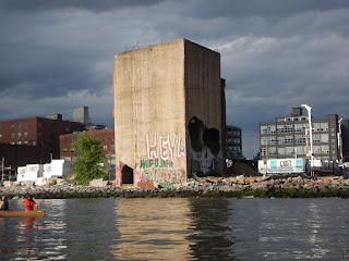A view from the East River of an ruined building with graffiti that makes it look like a skull