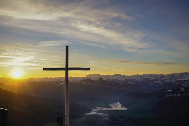 A picture of a cross with a sunset view in the valley