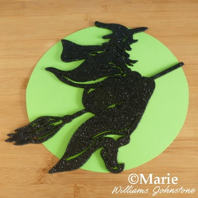 $1 store black glitter witch on green paper circle backing