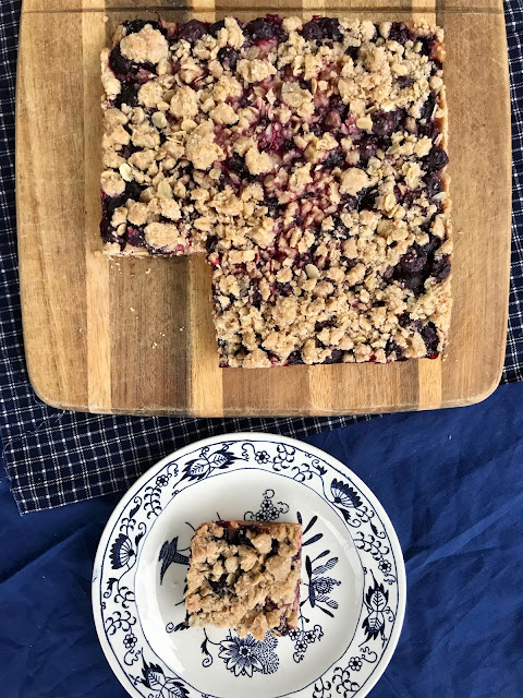 Blueberry bars made with oatmeal and cinnamon make a delightful and easy dessert. The oatmeal crisp topping also doubles as the crust and frozen blueberries make this a treat to whip up all year round.