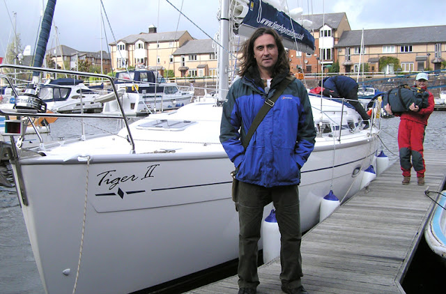 Picture of the Archaeologist Neil Oliver standing by a yacht called Tiger II