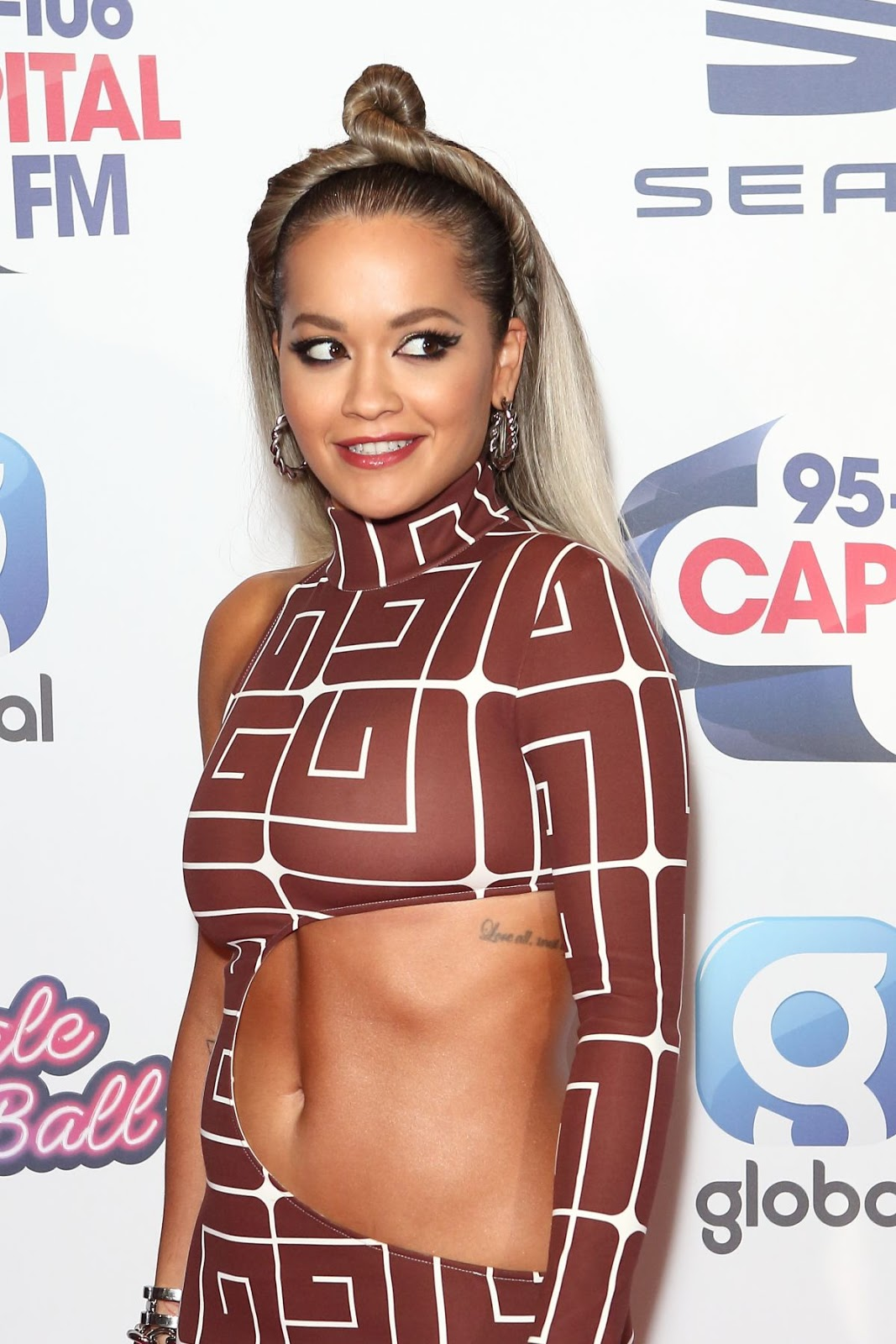 Rita Ora flashes her midriff in a quirky cut-out dress and matching boots at Capital's star-studded Jingle Bell Ball
