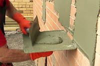 Bir sıvacının sıva ile tuğla bir duvarı sıvaması
