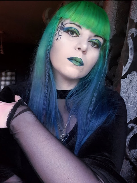 A woman with neon-green to royal blue gradient hair, neon green at the top, fading through emerald green and aqua to the deep blues of the ocean. She has pale skin, and dramatic make-up. She is wearing eyeshadow in neon green, emerald green and bright blue, with metalic violet and black eyeliner in a 'winged' style, and black mascara. She has vines in a swirling design drawn on the right side of her face. She is wearing green metallic lipstick outlined in metallic violet. She is wearing a high-necked velvet top with a v-neck style mesh insert, and with one arm across her body she is showing that the sleeves of the top are mesh, terminating in a point at her hand. She is wearing a pewter pendant of a winged Grim Reaper from Alchemy Gothic. Her hair is long, with a fringe and a thin braid either side of her face. She is in a room with dark purple walls.