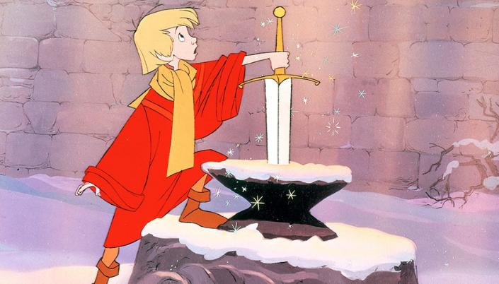 Imagem: o pequeno Arthur, um garoto com cabelos loiros, olhos pretos, uma roupa vermelha com detalhes laranja e um cachecol amarelo, encostando em uma espada cravada numa pedra num lugar coberto de neve.