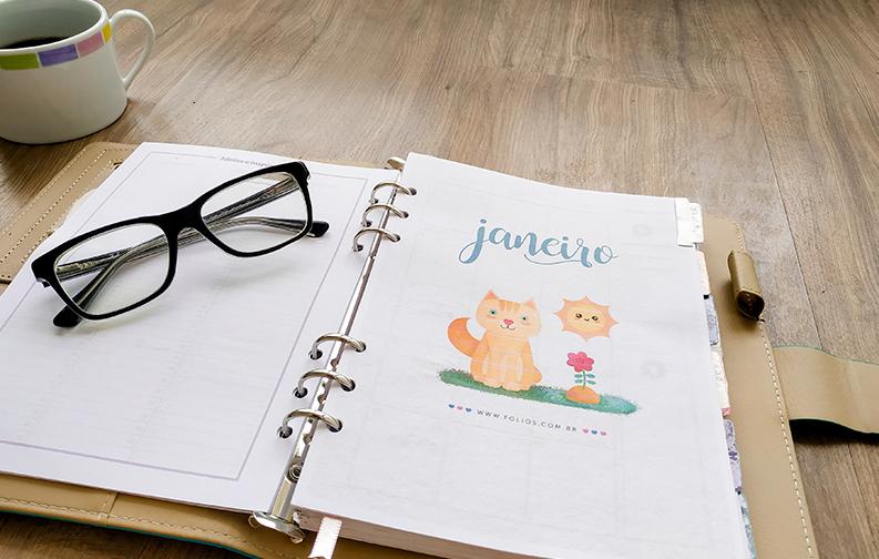 """A imagem mostra uma agenda aberta, na primeira página do mês de janeiro. A página mostra um gato ao lado de uma flor, com a palavra """"janeiro"""" localizada no topo. Em cima da página esquerda, em branco, está um óculos preto. No topo esquerdo da imagem, é possível ver uma xícara de café posicionada ao lado da agenda"""
