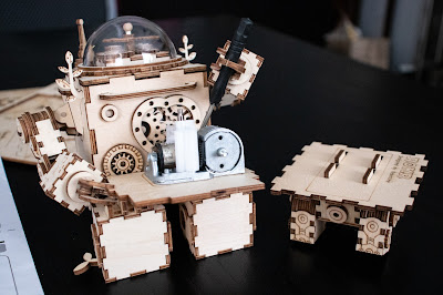 A wooden robot with a screen driver assembling a small music box while sitting next to wooden legs.