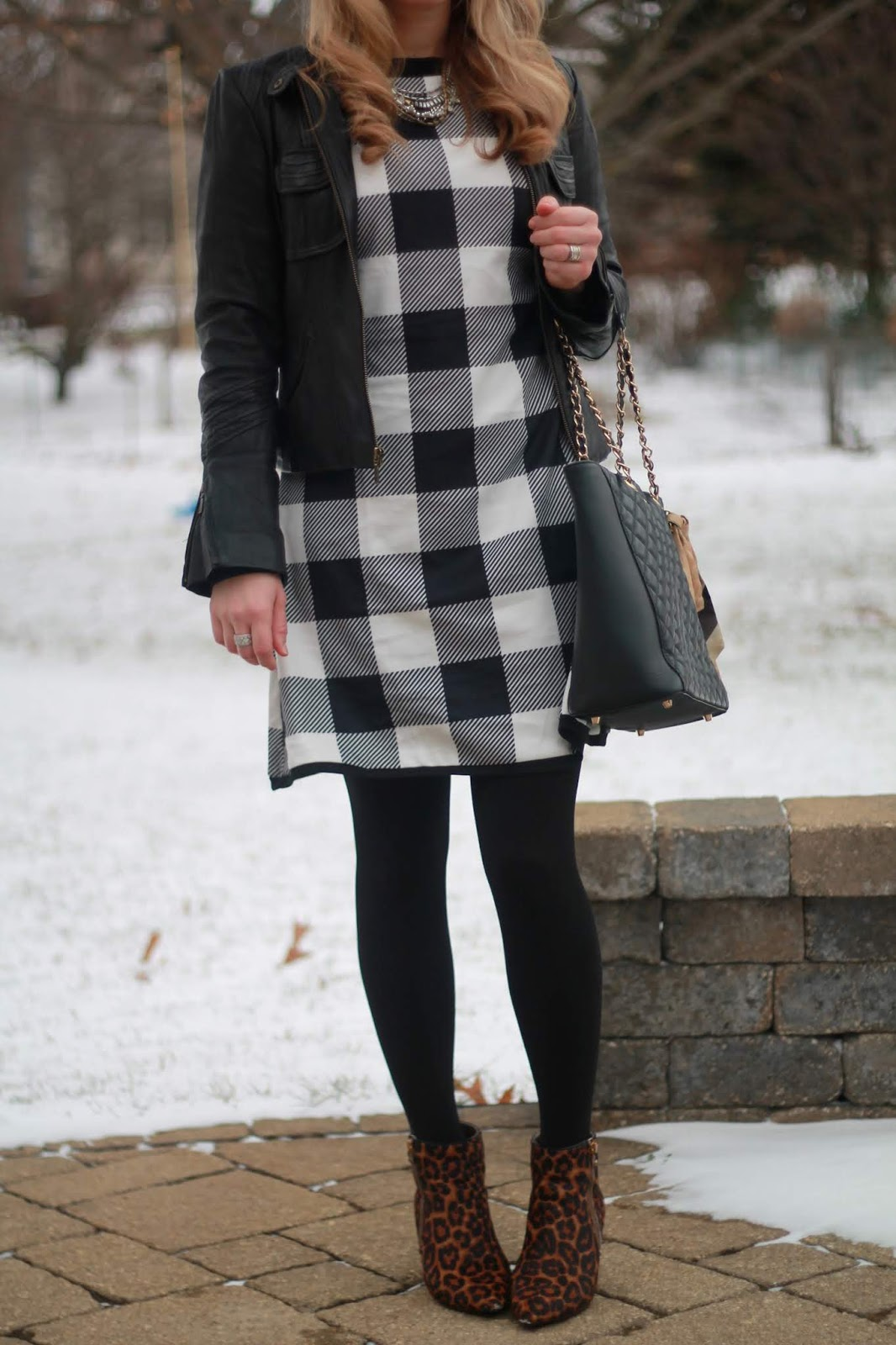 black quilted tote, black and white plaid dress, leather moto jacket, leopard booties
