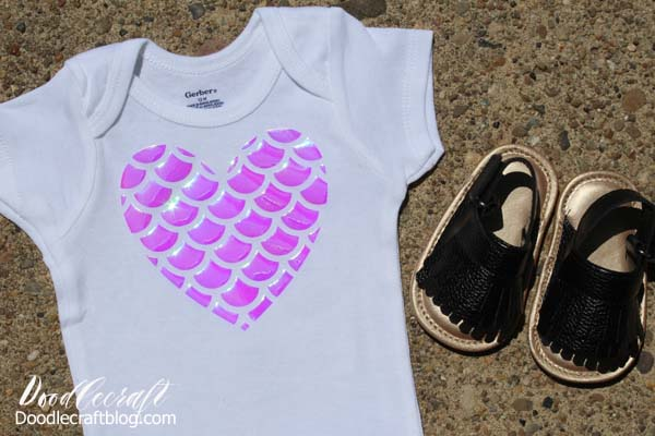 Pink Shimmering Holographic Mermaid Scales cut in a Heart shape and ironed on a Onesie with Cricut EasyPress 2.