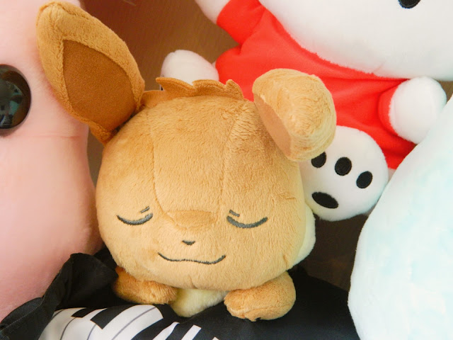 A photograph of a sleeping fox-looking Pokemon plush