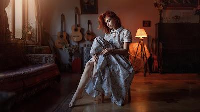 Chica pelirroja sentada en una silla con elegante vestido en el salón de su casa