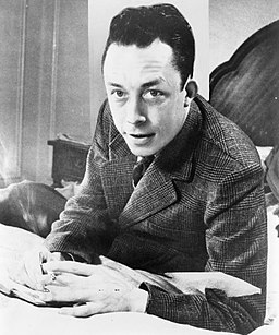Photo of Albert Camus, seated at desk, smoking cigarette