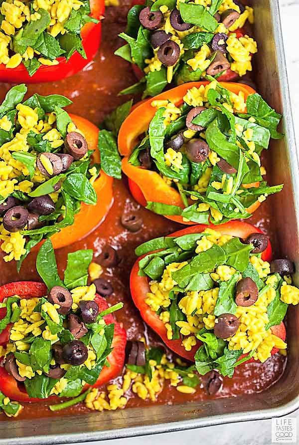 Vegetarian stuffed peppers a top tomato sauce in baking dish ready to go in the oven