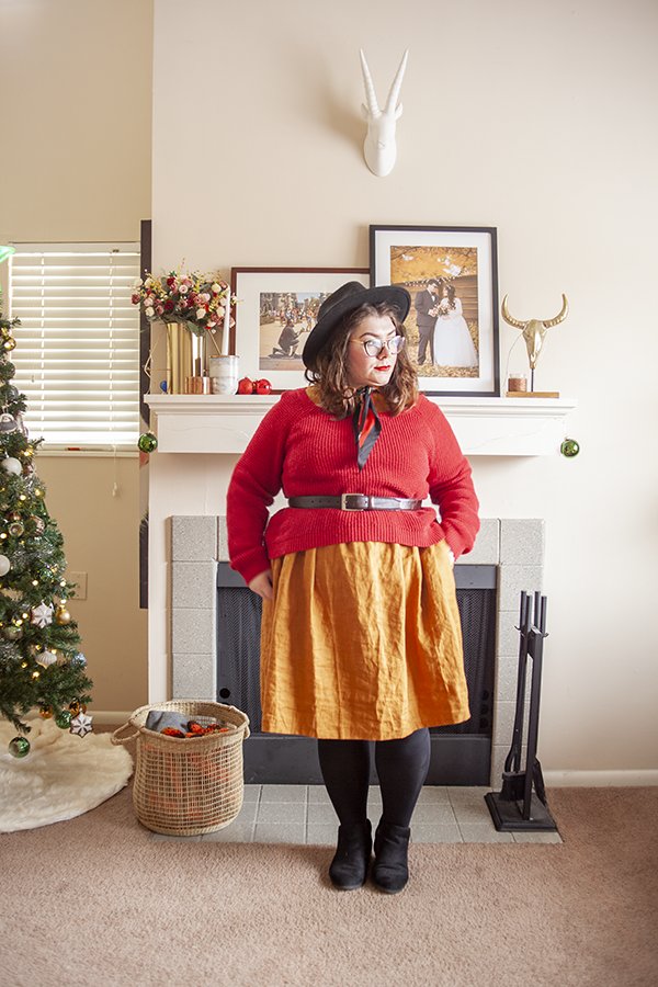 An outfit consisting of a red sweater belted over an ochre colored collared linen dress with black ankle boots.