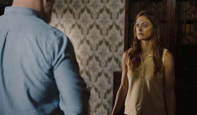 Light from Light 2019 movie still featuring Jim Gaffigan and Marin Ireland discussing ghosts and the paranormal