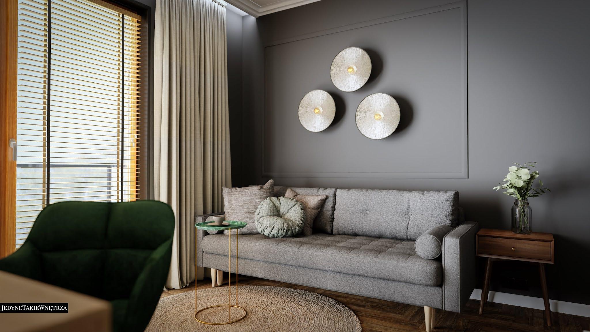 Elegancki salon z szarą kanapą, obok której stoi stolik kawowy na pozłacanych nóżkach. Ścianę zdobią listwy ścienne.