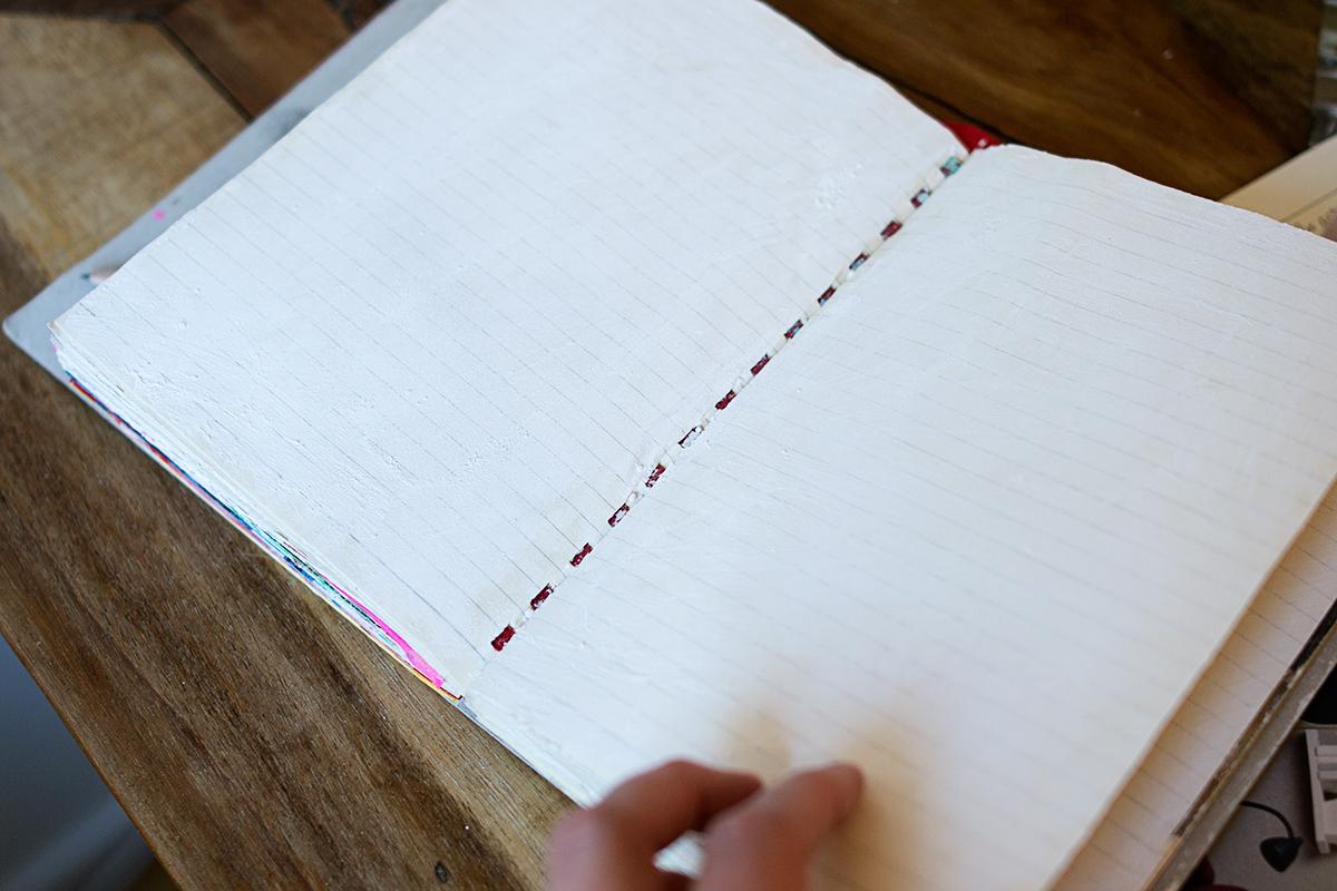 Anteckningsbok med sidor som är målade med gesso.