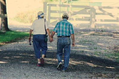 A photo of old couple walking on Road