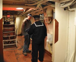 Sailor explains a display to a man