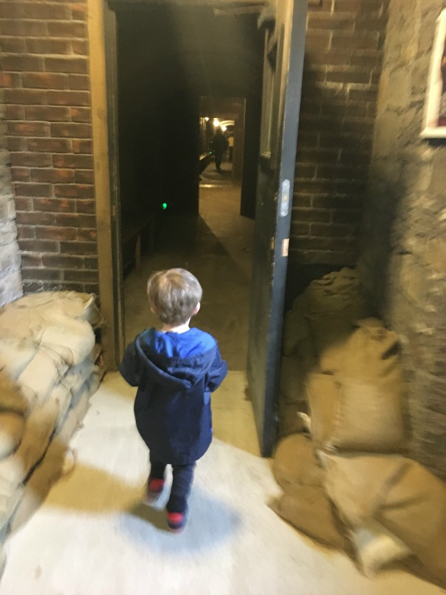 a-toddler-explores-cardiff-castle-world-war-two-shelters-view-of-inside-castle-tunnel-with-toddler-walking-through-doorway-surrounded-by-sandbags