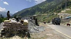 Indian paramilitary soldiers keep guard as Indian army convoy moves on the Srinagar- Ladakh highway at Gagangeer, north-east of Srinagar