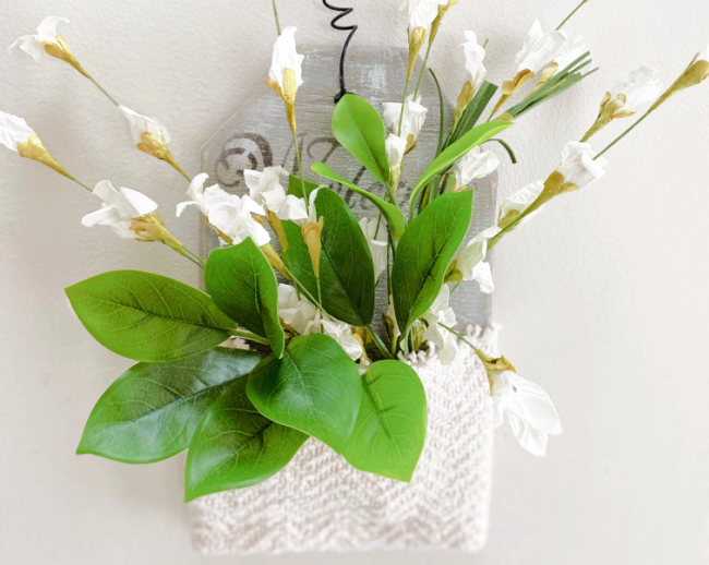 wall pocket with white flowers and greens