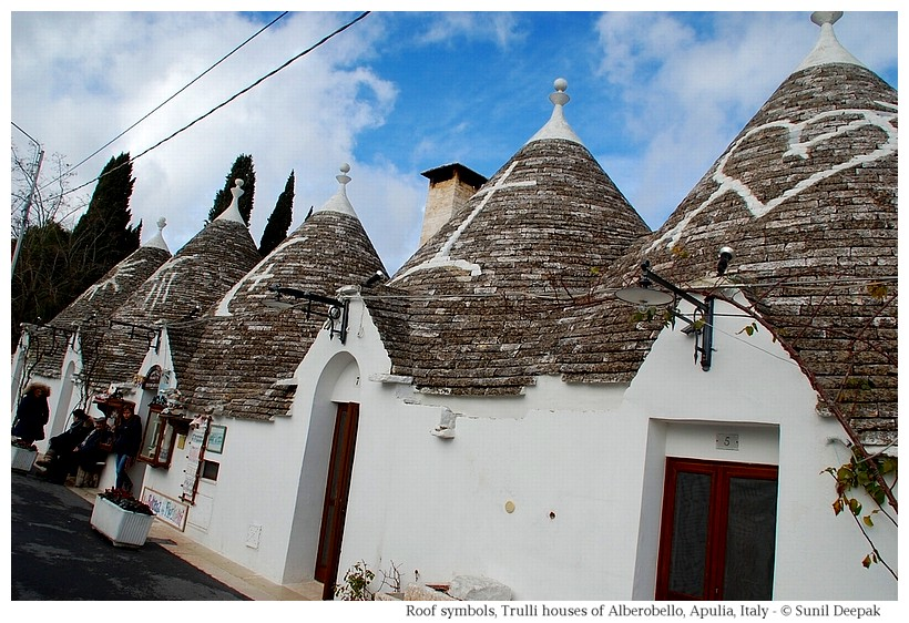 Trulli houses in Alberobello with signs painted on the roof - Photographs by Sunil Deepak