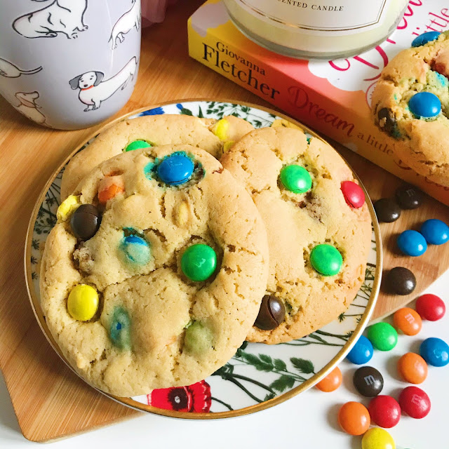 M&M cookie on flower trinket dish on heart shaped wooden chopping board with cath kidston mug to the left, book to the right with candle on top