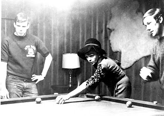 A photograph of Judy Garland, well-dressed and leaning over a pool table. There are two young men next to her.