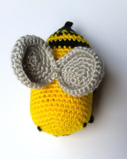 Top view of Bee Number Three showing silver wings. Each wing is constructed from a crocheted circle. The edge rounds are worked even to make them curl. They are attached to each other in a figure-8 or infinity shape and then attached to the back (body) of the bee.