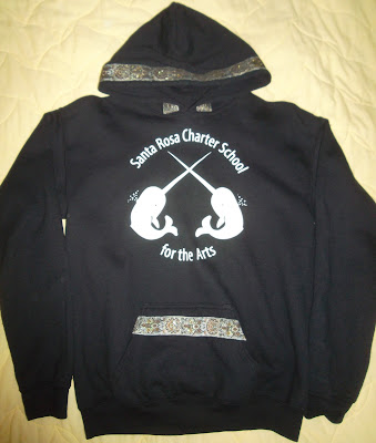 Black hoodie with image in white of two narwhals with crossed horns. Letters in white, above and below the image, read 'Santa Rosa Charter School for the Arts.' The garment's hood and the top of its 'Kangaroo Pocket' are edged with gold-brocade trim.