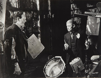 A photo from the set of Frankenstein with the monster (Karloff) facing the director, James Whale.