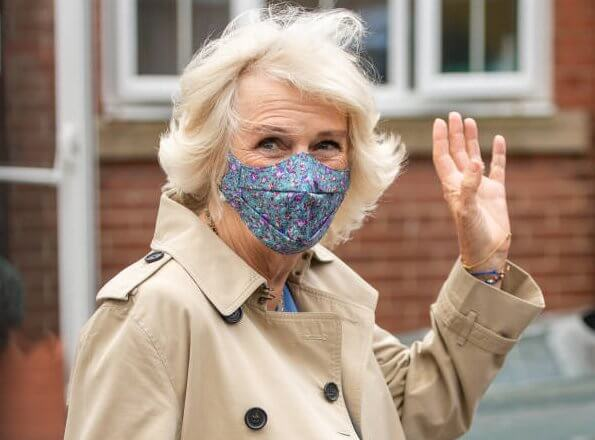 Camilla, Duchess of Cornwall wore a blue wool midi dress, and the mid-length chelsea trench coat from Burberry. British luxury brand Burberry
