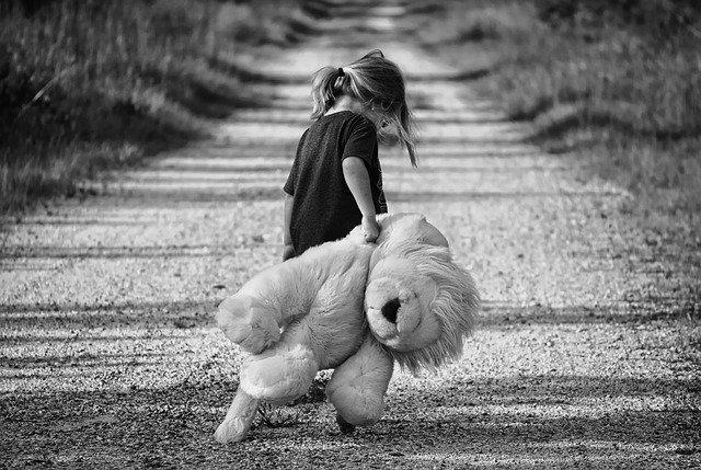 potret hitam putih seorang gadis dengan boneka ditangannya